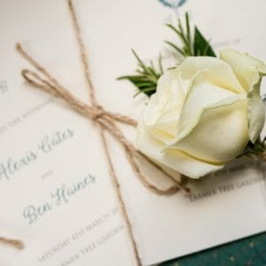 Rose rests on the wedding stationery - Larmertree Gardens wedding