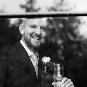 Groom stands by the window at the Larmertree Gardens - Wiltshire wedding