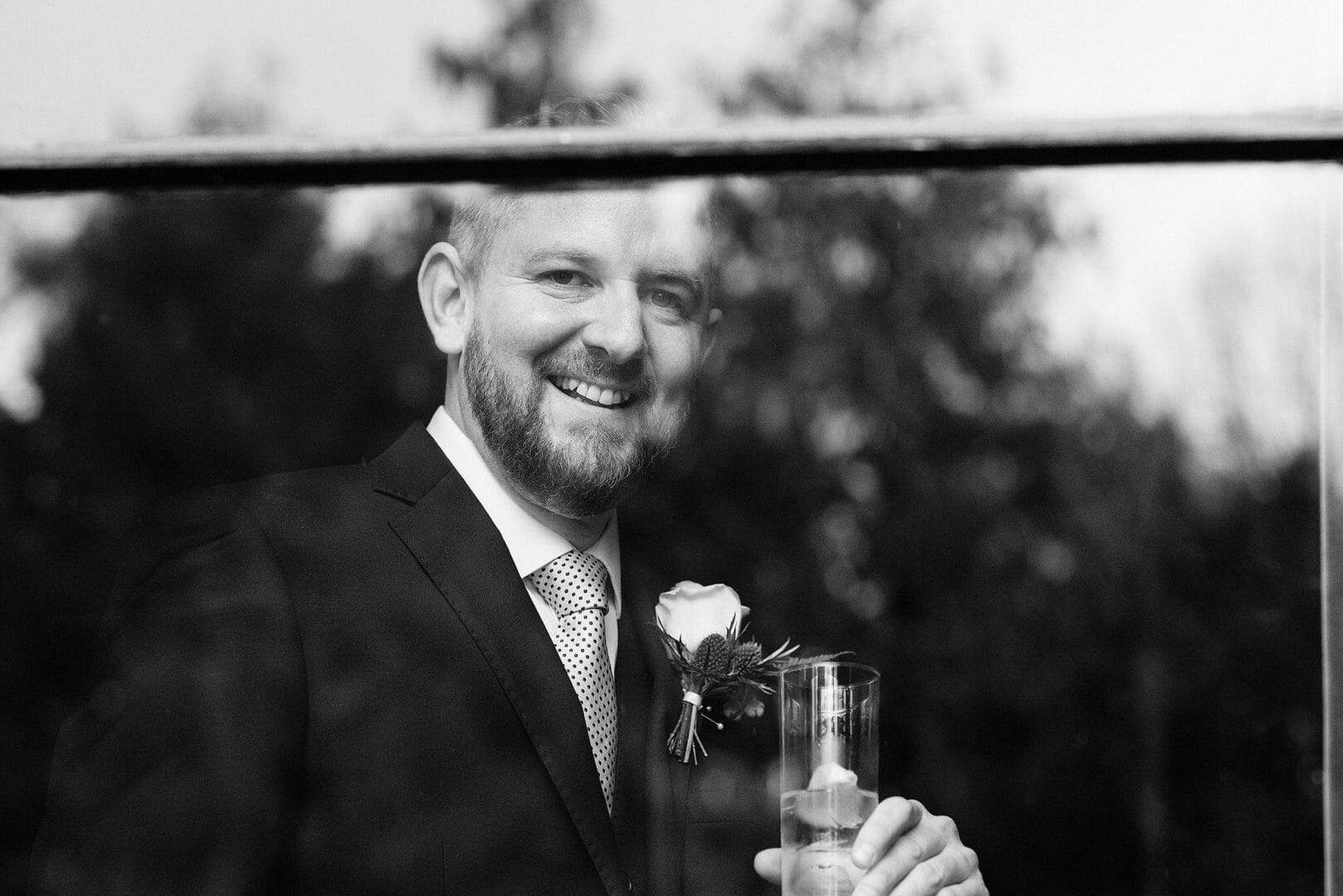 Groom stands by the window at the Larmertree Gardens – Wiltshire wedding