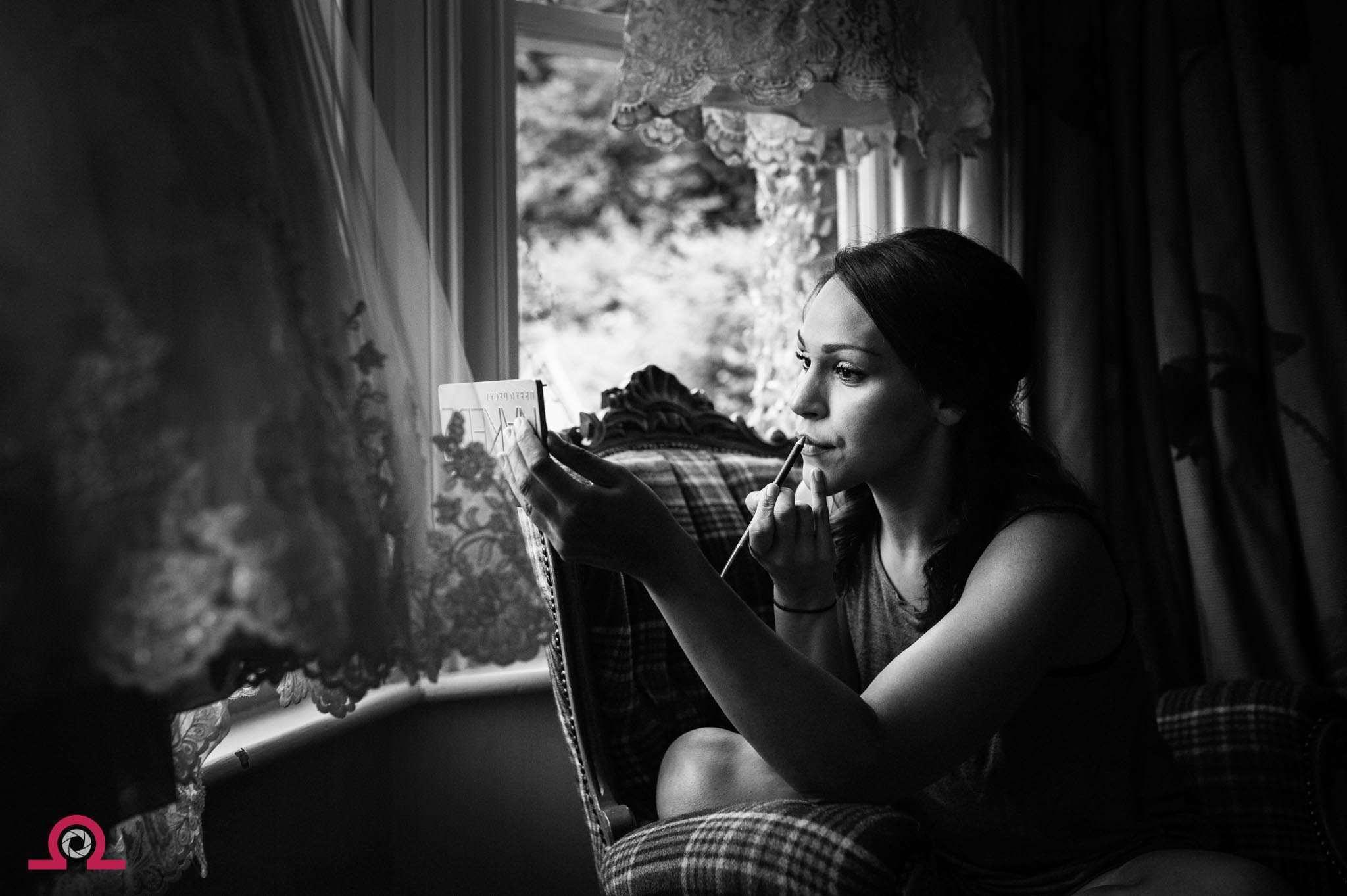 Bride applying her makeup in the window -Larmertree Wedding