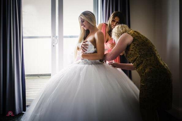 Bride putting on her wedding dress at the Sandbanks Hotel