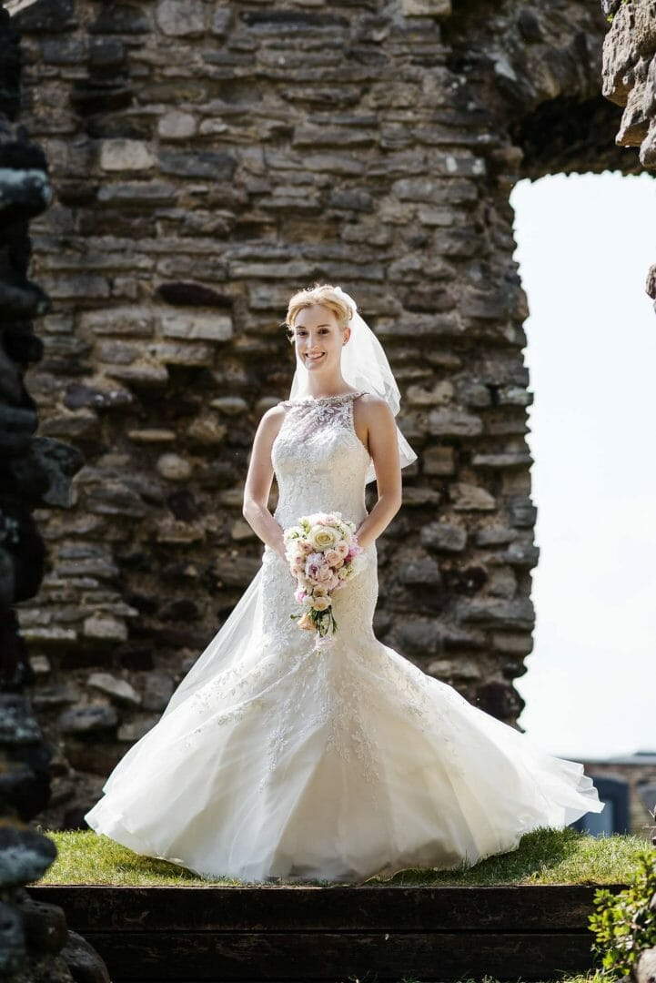 Bride in weddingdress poses in ruins by Kings Arms Hotel