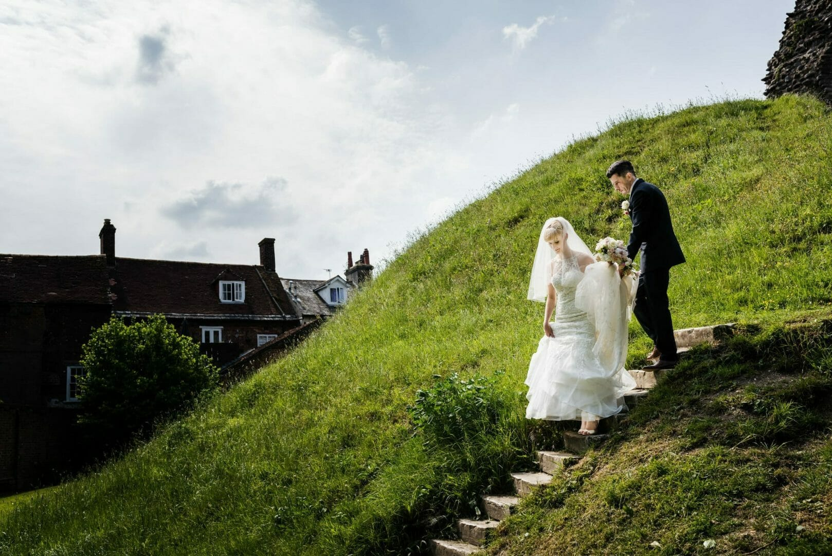 Bride and groom walking down castle hill