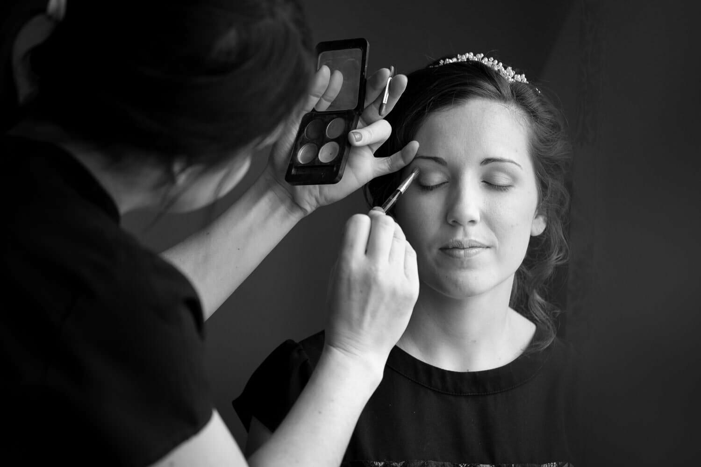 Bride having makeup applied by window