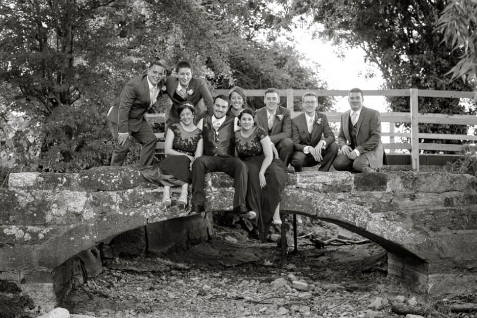 Gromsmen and Bridesmaids hanging out on a stone bridge