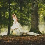 Bride running through forest