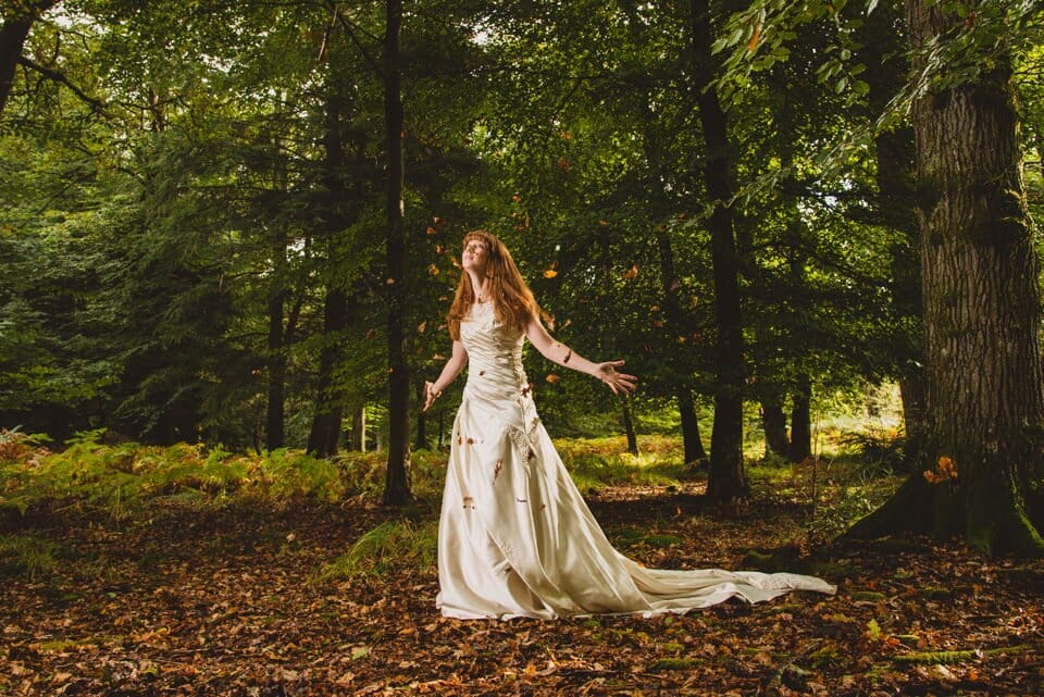 Bride throwing autumn leaves in the air