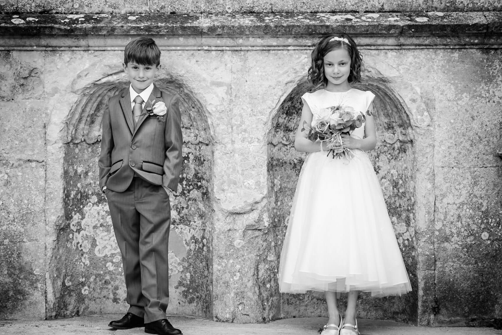 Pageboy and flower girl pose infront of lulworth castle in black and white
