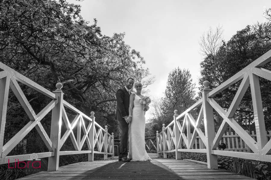 Bride and groom pose on bridge in b&w